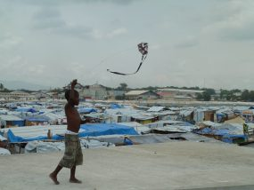 Child playing with kite in tent camp after earthquake, Port-au-Prince, Haiti, 2010.
