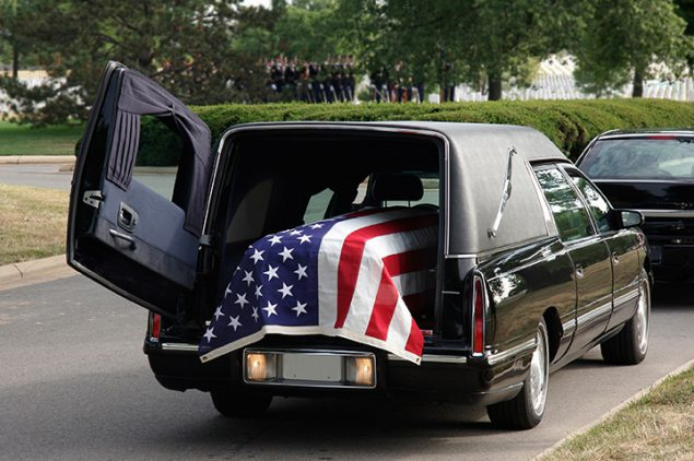 coffin loaded into a hearse