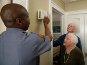 Older Adult Couple with Fireman testing fire alarm