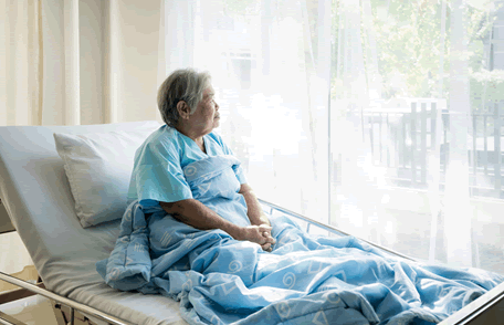 Woman in a hospital bed looking out of a window