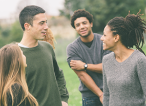 Image of young adults having a conversation outdoors