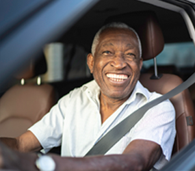 Image of a smiling older man driving a car
