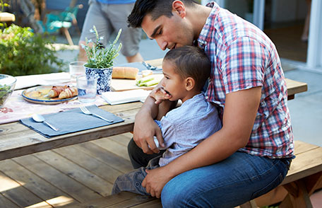 Father sitting at picnic table and holding son in lap
