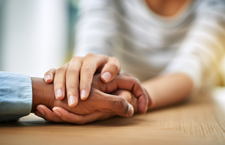 close-up of the hands of two people holding hands