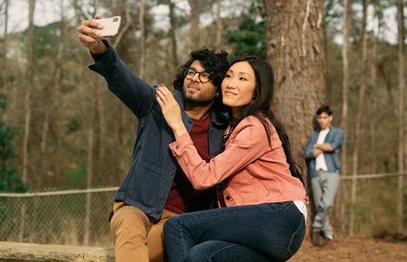 Image of a young couple taking a selfie while a young man watches in the background