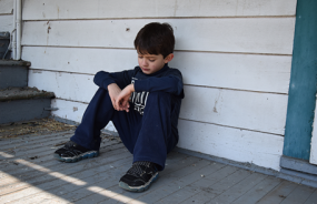 Image of a boy sitting alone