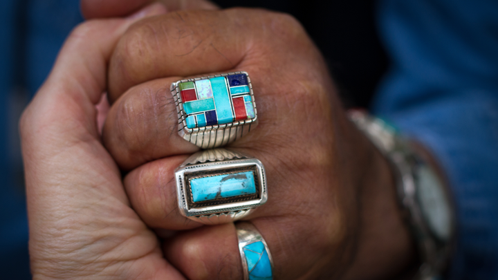 View of a handshake featuring rings with Native American design