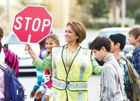 Woman crossing guard holding stop sign while school children pass by.