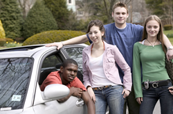 Photo: Teenagers standing around a car
