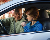 photo: teenage girl putting on her seatbelt in the driver seat while her father watches from the passenger seat