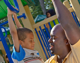 photo: Dad playing with son on a playground