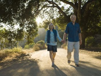 older couple walking on a sunny road in the woods