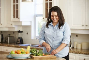 image of a woman chopping vegetables in a kitchen