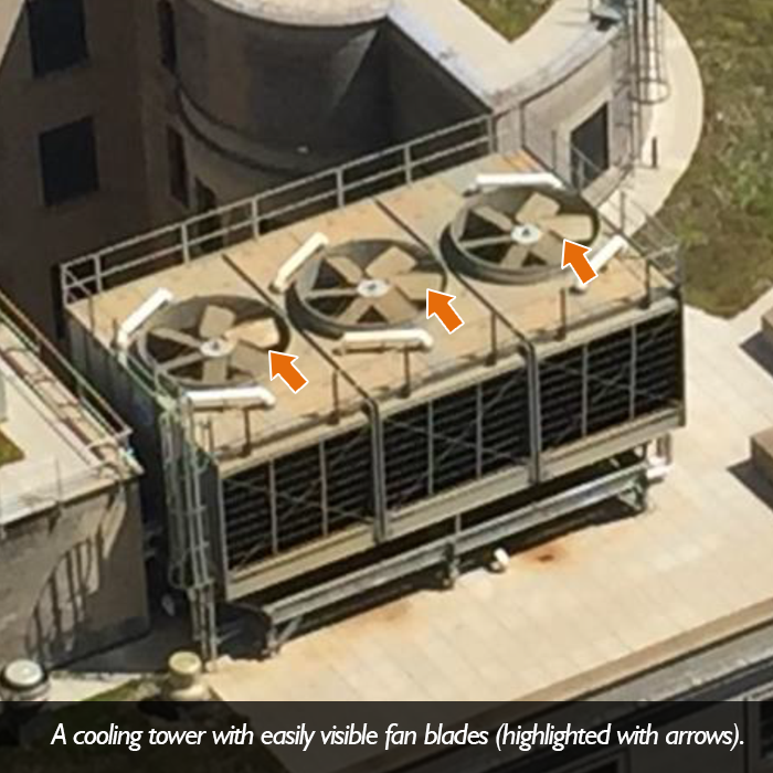 A picture of a cooling tower with easily visible fan blades.