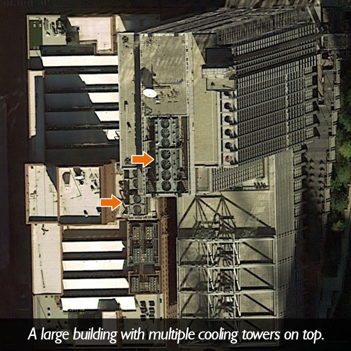 An aerial picture of a large building with multiple cooling towers on top.