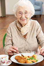 PHot of an elderly woman smiling and eating supper.
