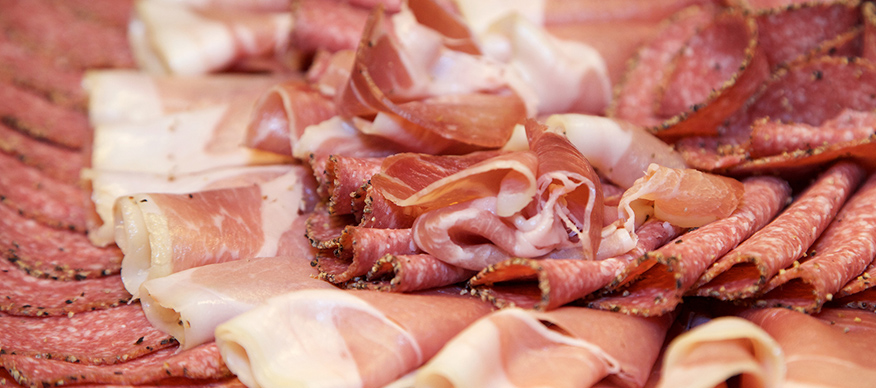 Close-up shot of a platter of cold cuts including salami, pepperoni and cured ham.