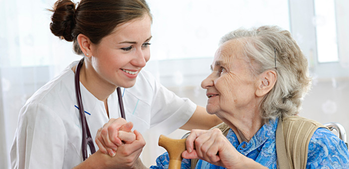 Doctor talking to elderly lady in nursing home