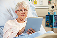 Senior Female Patient Relaxing In Hospital Bed With Digital Tabl