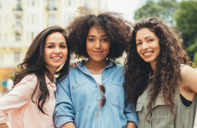3 young multi-ethnic women standing in a courtyard