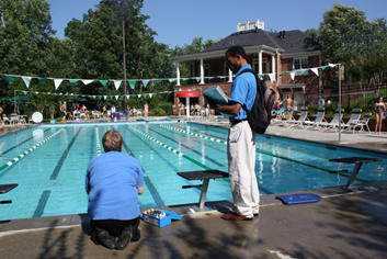 staff testing the pool chemicals next to diving platform