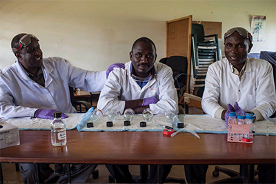 Image of some lab techs with bioassay supplies.