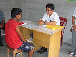 A young boy is interviewed by a health-care worker as part of CDC activities in Iquitos, Peru.