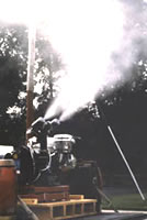 Fogging machine spraying insecticide in an open area