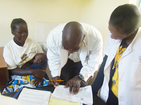KEMRI Clinical Officer Paul Ogai reviews a prospective participant's vaccination card during trial enrollment at the KEMRI/CDC site in Kenya. (Alan Rubin, KEMRI)