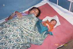 Picture of a mother and her baby in a hospital bed.