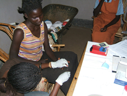 A worker takes a blood sample from a mother in Oyugis, Kenya to compare malaria levels between sprayed and non-sprayed regions. Credit: Adam Wolkon, CDC