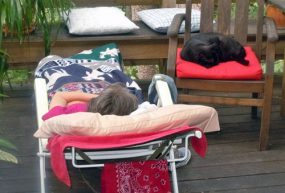 ME/CFS patient outside in lounge chair resting with her cat