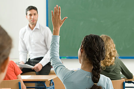 female student raises her hand to ask a question of the teacher, sitting front of class
