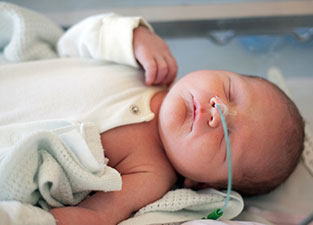 baby with oxygen tube
