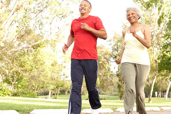 Man and woman outdoors walking for exercise.