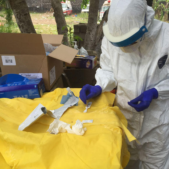 A disease detective wearing protective equipment conducts field testing of samples in Liberia