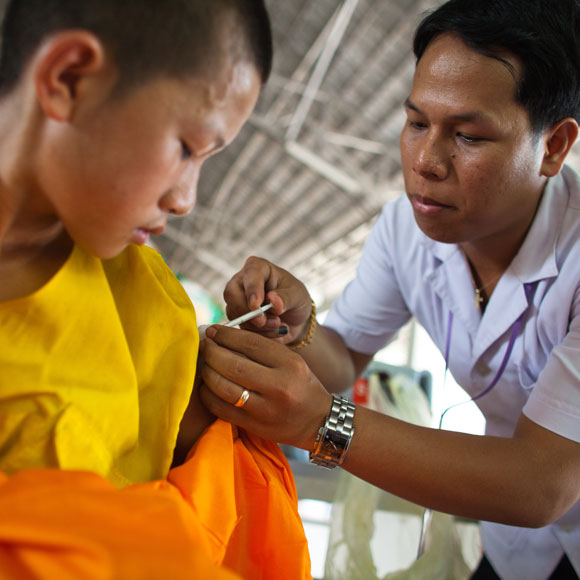 A male nurse giving a vaccine to a young monk in orange robes