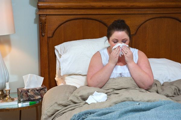 A woman in bed, blowing her nose into a tissue