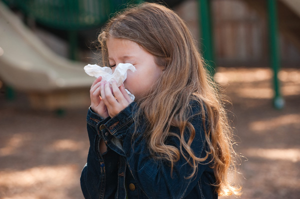 A young girl blowing her nose into a tissue