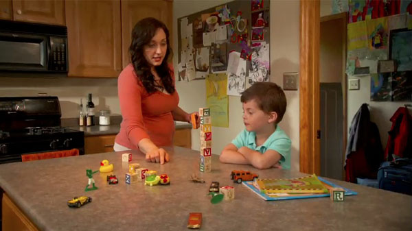 A woman stacking blocks with her young son while instructing him