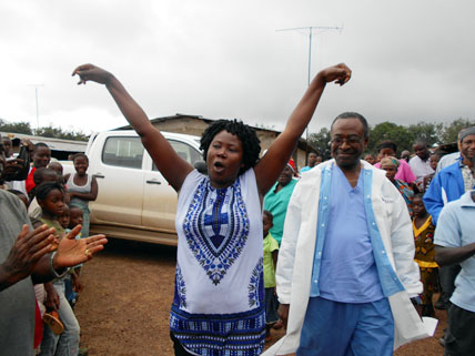 Ebola survivor, accompanied by medical director, being welcomed by her community - Firestone District, Liberia, 2014