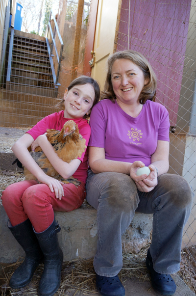 Young girl with her mom holding a hen