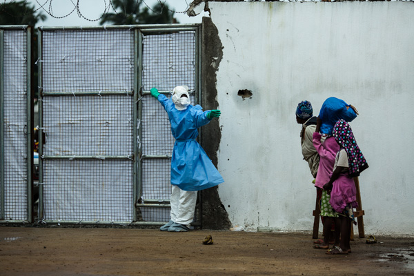 A healthcare worker opening a door for an ambulance at Ebola Treatment Unit in Liberia, 2014