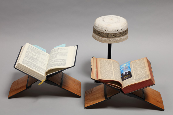 The Qur'an and Bible are sitting on traditional hand-carved rehals
