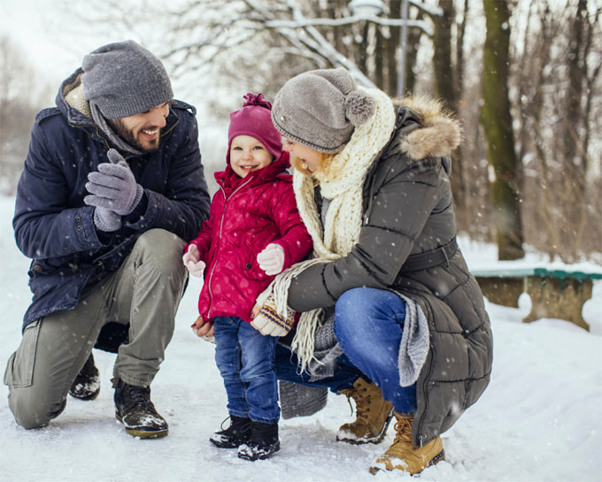 father and mother with toddler in the snow