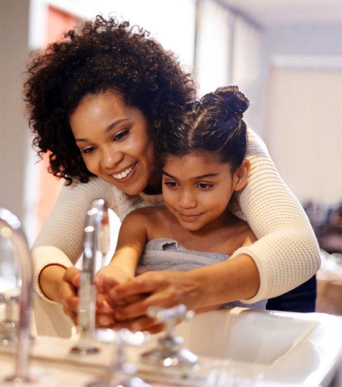 mother helping daughter wash her hands