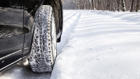 closeup of a car's front tire on a snow-covered road