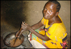 A woman in Kenya cooking over an open fire