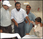 Dr. Jawad Ashgar, in Pakistan, visits a child who survived the flood waters for 12 hours before rescue.