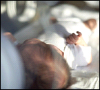 An infant laying in a hospital bed